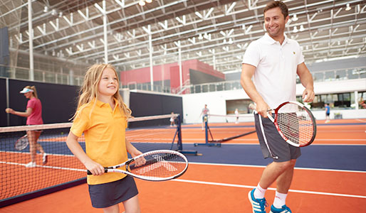 A man and a girl playing tennis at David Lloyd.