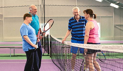 A male and female tennis pair chatting and laughing to another mixed pair on the other side of the net.