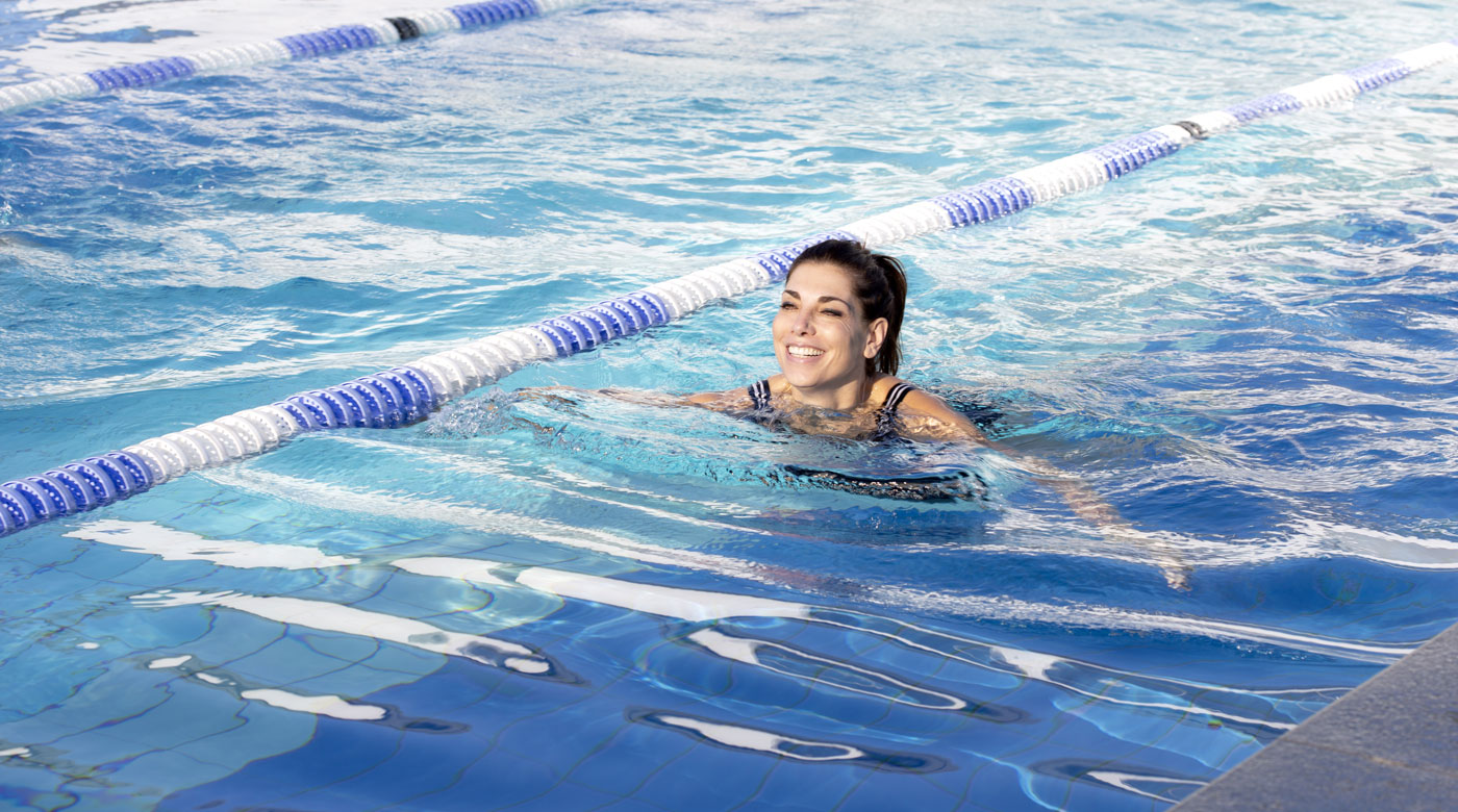 Image of lady swimming in the outdoor pool
