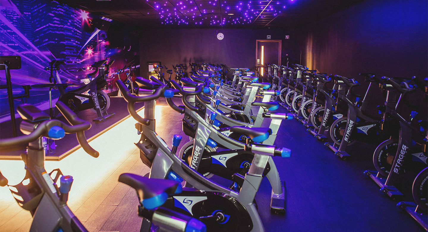 A large amount of stationary bikes in a brightly coloured room.