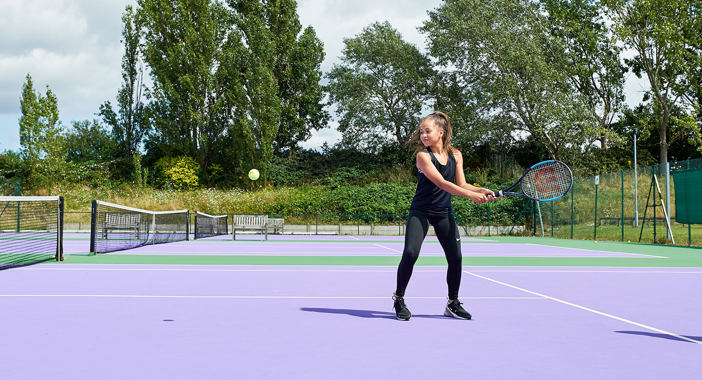 Image of a young girl playing a backhand on the tennis court at David Lloyd Purley