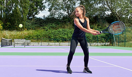 Image of a girl hitting a backhand on an outdoor tennis court
