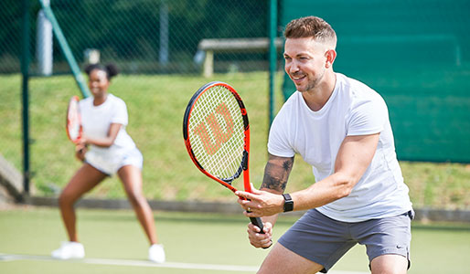 Image of a man and a woman playing doubles tennis on an outdoor court