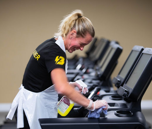 Image of lady cleaning treadmill